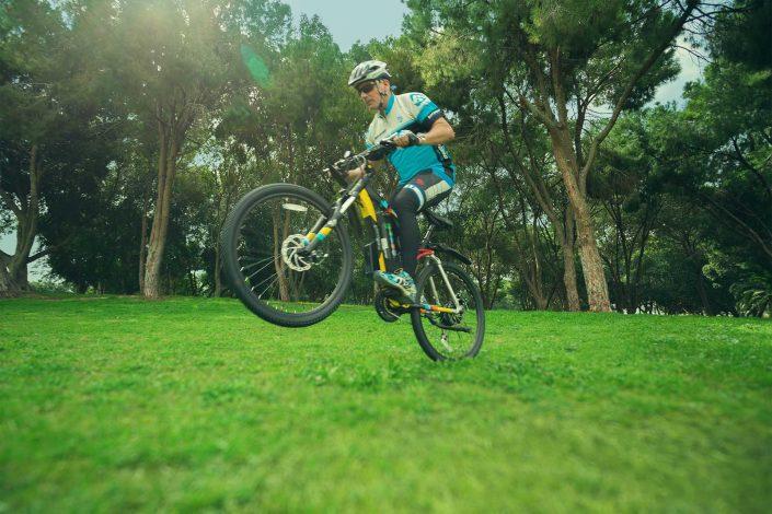 רוכב על אופניים הרים חשמליים אנדורו של גרין בייק בנסיעה על הדשא